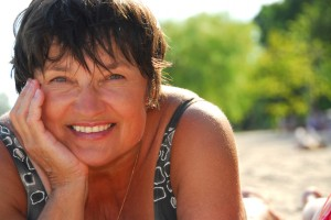 Portrait of a mature woman lying on a sandy beach
